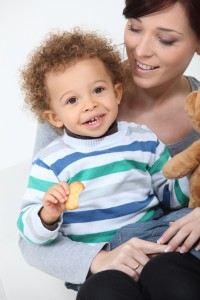 Little boy with teddy and biscuit